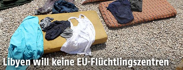 Schäbige Matratzen mit Kleidung darauf verstreut