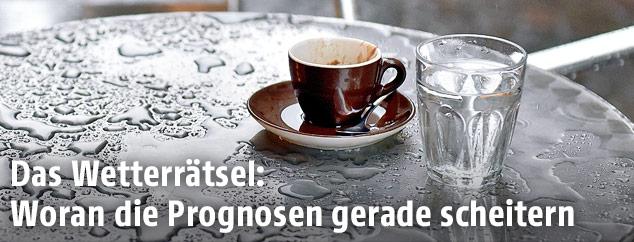 Eine Kaffeetasse auf einem verregneten Tisch
