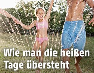 Vater und Tochter in Badekleidung kühlen sich mithilfe eines Rasensprengers ab