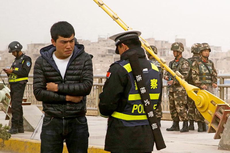 Polizei bei der Kontrolle von Passanten in Xinjiang, China