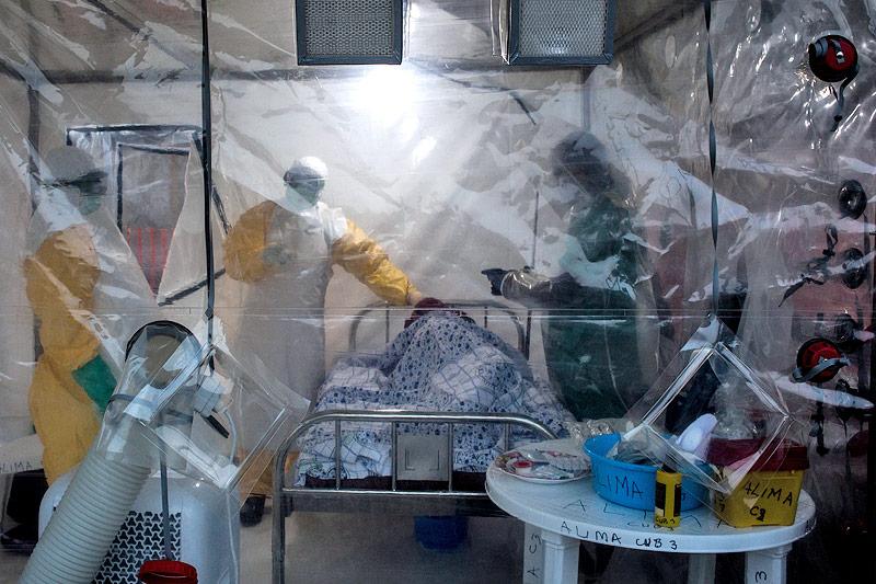 Mediziner mit Schutzanzügen neben einem Patienten in einem abgeschlossenen Raum