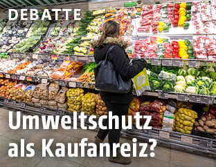 Frau steht in einem Supermarkt vor einem Regal mit Gemüse